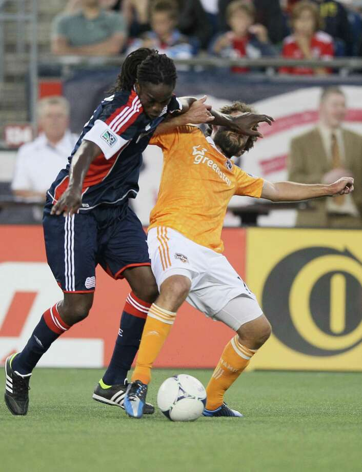 FOXBORO, MA - MAY 19:  Adam Moffat #16 of the Houston Dynamo is hit by Shalrie Joseph #21 of the New England Revolution in the first half on May 19, 2012 at Gillette Stadium in Foxboro, Massachusetts. Photo: Elsa, Getty Images / 2012 Getty Images