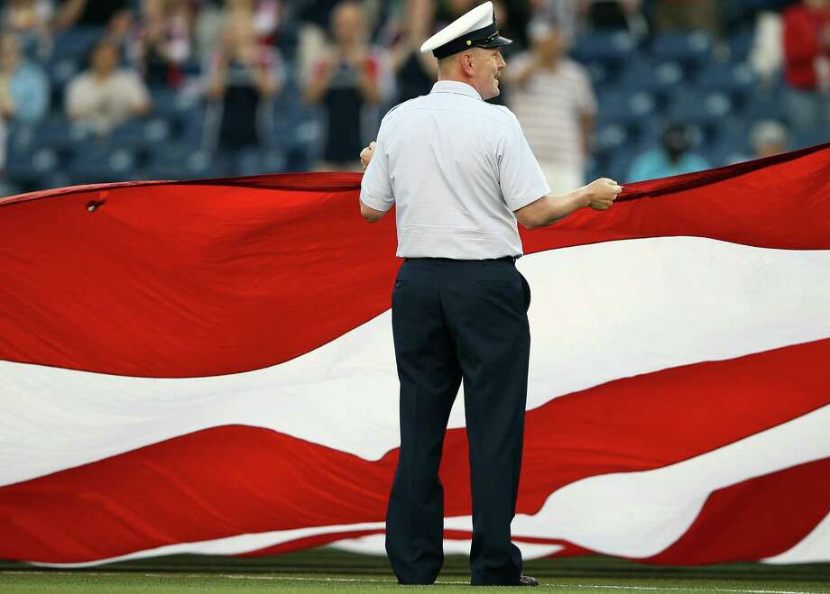 FOXBORO, MA - MAY 19:  A member of the U.S. military holds part of a giant flag in an on field presentation before the game between the New England Revolution and the Houston Dynamo on May 19, 2012 at Gillette Stadium in Foxboro, Massachusetts. Photo: Elsa, Getty Images / 2012 Getty Images