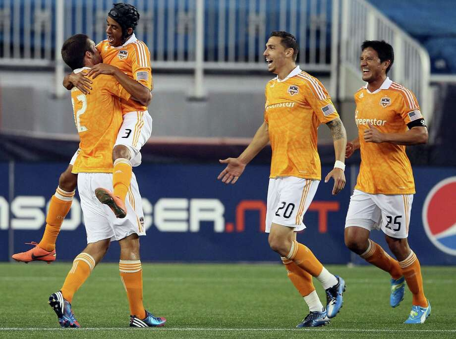 FOXBORO, MA - MAY 19:  Will Bruin #12 of the Houston Dynamo is congratulated by teammates Calen Carr #3, Geoff Cameron #20 and Brian Ching #25 after Bruin scored in the first half against the New England Revolution   on May 19, 2012 at Gillette Stadium in Foxboro, Massachusetts. Photo: Elsa, Getty Images / 2012 Getty Images
