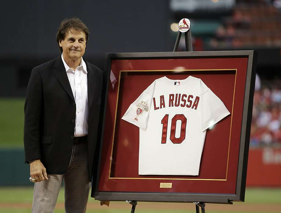 Former St. Louis Cardinals manager Tony La Russa stands next to his framed jersey at the end of a ceremony to retire his number before a baseball game between the Cardinals and the Atlanta Braves, Friday, May 11, 2012, in St. Louis. La Russa retired last fall after leading the Cardinals to their second World Series championship in 16 seasons with him as manager. (AP Photo/Jeff Roberson) Photo: Jeff Roberson, Associated Press