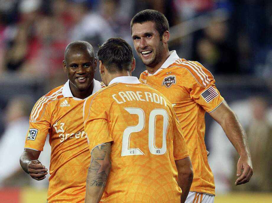 FOXBORO, MA - MAY 19:  Luiz Camargo #17 of the Houston Dynamo is congratulated by teammates Geoff Cameron #20 and Will Bruin #12 after Camargo scored a goal in the second half against the New England Revolution on May 19, 2012 at Gillette Stadium in Foxboro, Massachusetts.The New England Revolution and the Houston Dynamo tied 2-2. Photo: Elsa, Getty Images / 2012 Getty Images