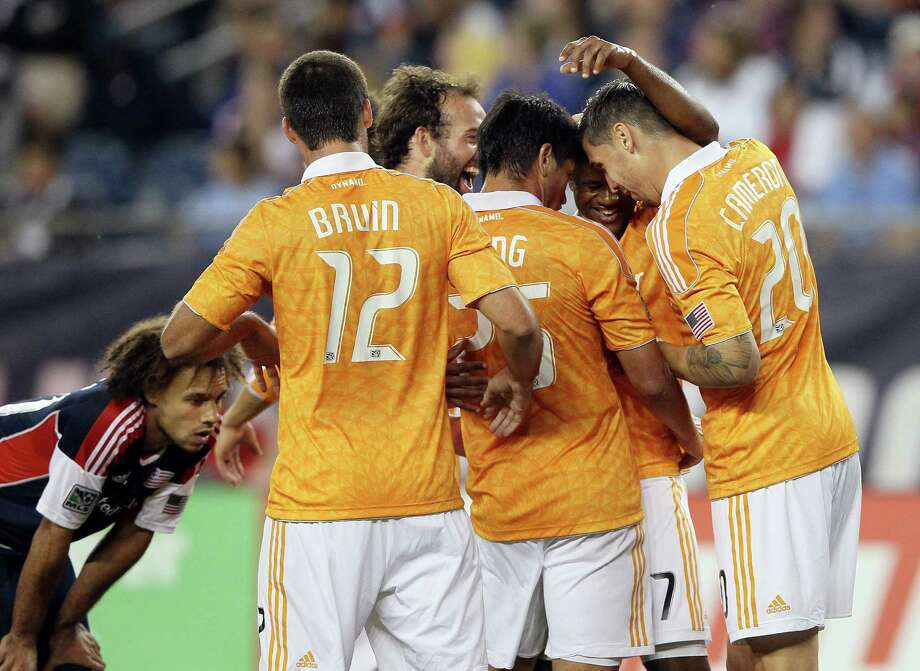 FOXBORO, MA - MAY 19:  Luiz Camargo #17 of the Houston Dynamo is congratulated by teammates Geoff Cameron #20,Brian Ching #25 and Will Bruin #12 after Camargo scored a goal to tie the game as Kevin Alston #30 of the New England Revolution stands by on May 19, 2012 at Gillette Stadium in Foxboro, Massachusetts.The New England Revolution and the Houston Dynamo tied 2-2. Photo: Elsa, Getty Images / 2012 Getty Images