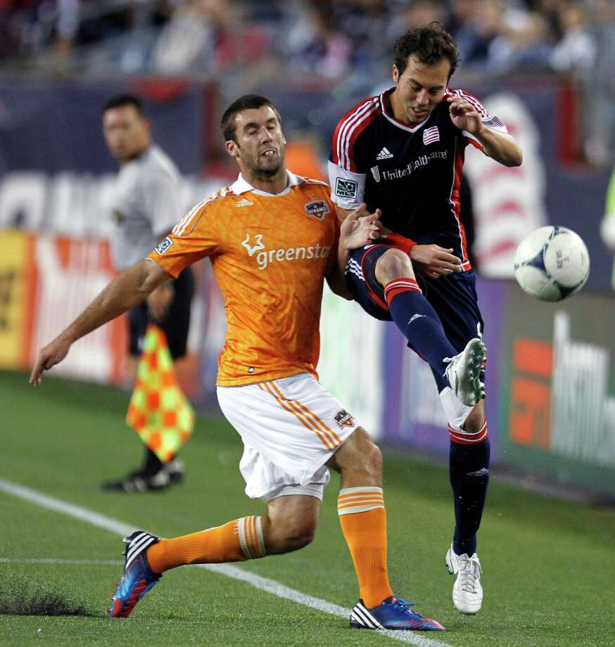 Houston Dynamo's Will Bruin, left, and New England Revolution's A.J. Soares compete for the ball in the second half of an MLS soccer game in Foxborough, Mass., Saturday, May 19, 2012. The game ended in a 2-2 tie. (AP Photo/Michael Dwyer) Photo: Michael Dwyer, Associated Press / AP