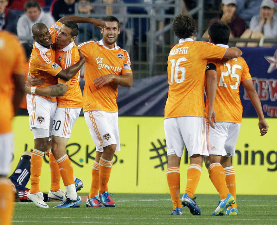 Houston Dynamo's Luiz Camargo, left, celebrates his goal with teammate Geoff Cameron (20) in the second half of an MLS soccer game against the New England Revolution in Foxborough, Mass., Saturday, May 19, 2012. The game ended in a 2-2 tie. (AP Photo/Michael Dwyer) Photo: Michael Dwyer, Associated Press / AP