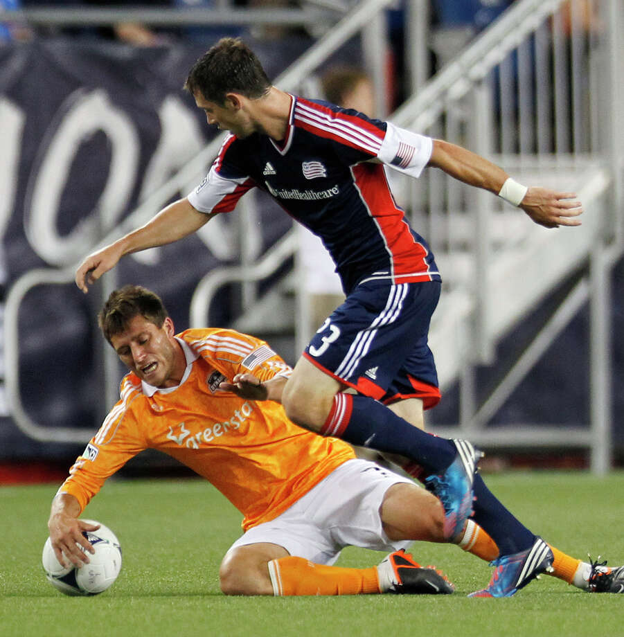 Houston Dynamo's Colin Clark, left, falls against the ball next to New England Revolution's Blake Brettschneider during the second half of an MLS soccer game in Foxborough, Mass., Saturday, May 19, 2012. The game ended in a 2-2 tie. (AP Photo/Michael Dwyer) Photo: Michael Dwyer, Associated Press / AP