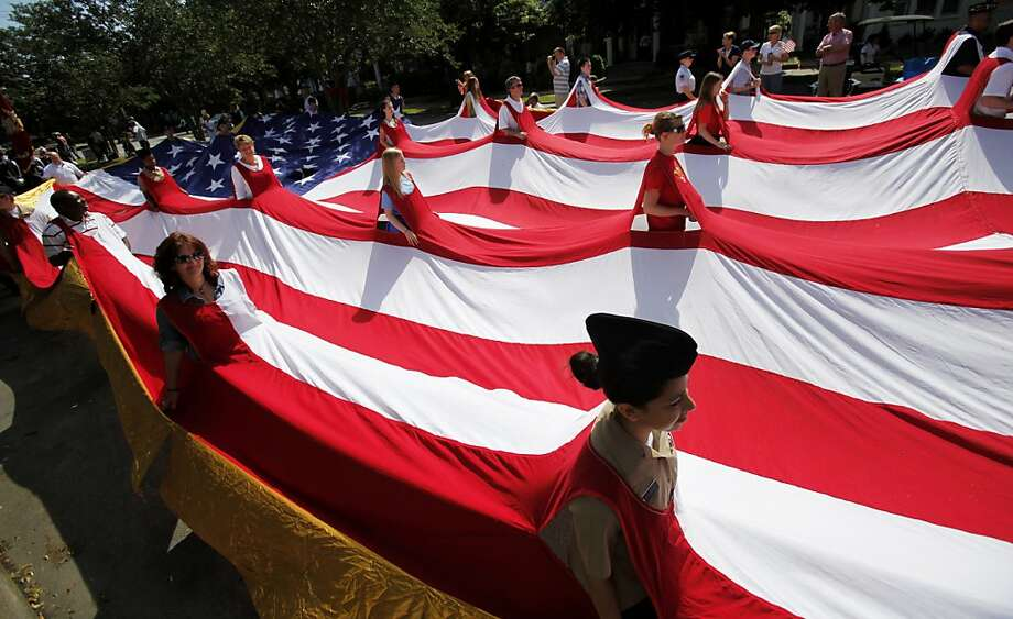 Parade paricipants wear a large American Flag along the route of the Welcome Home the Heroes Parade celebrating returning Iraq war veterans and their families in Richmond, Va. on Saturday, May 19, 2012. (AP Photo/Richmond Times-Dispatch, Dean Hoffmeyer) Photo: Dean Hoffmeyer, Associated Press