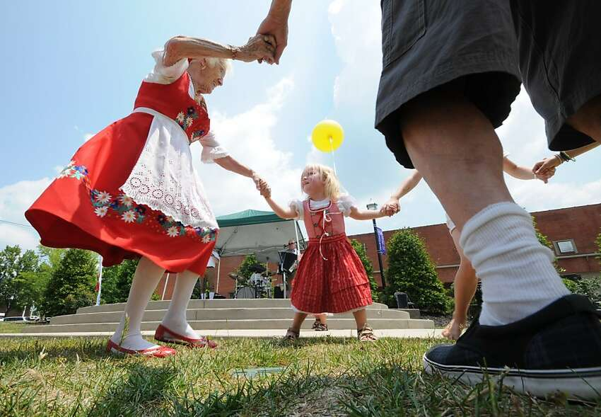 Marlene Pruecklmeier, center, dances a Bavarian dance with Lisa McGarvey, left, Saturday, May 19, 2012, at the 7th Annual Mai Fest in Cleveland, Tenn. The festival benefits the Montessori Kinder school in Cleveland. (AP Photo/Chattanooga Times Free Press, Tim Barber)