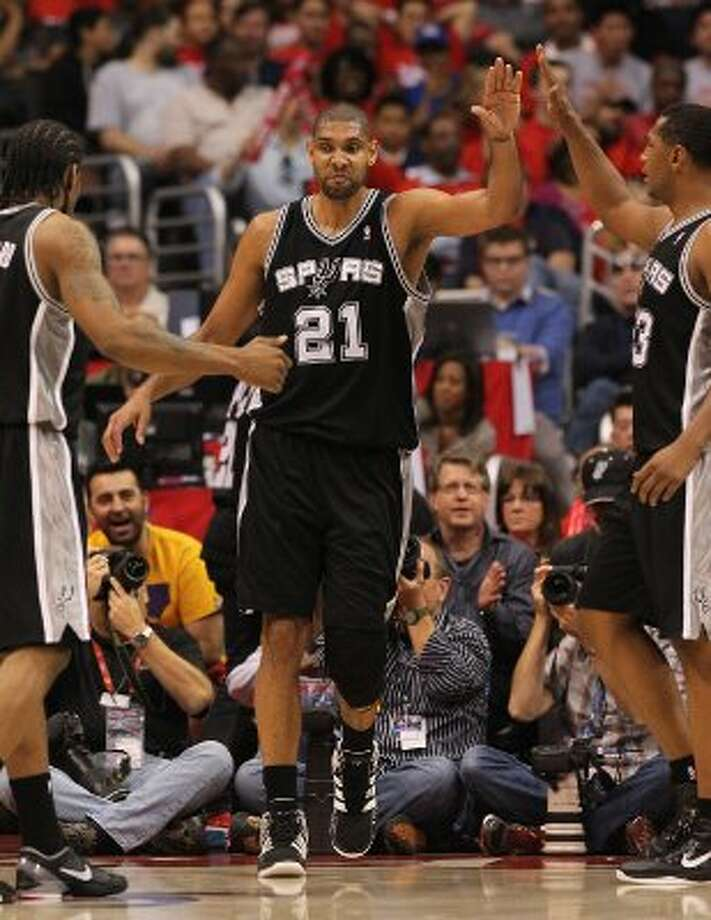 Spurs' Tim Duncan (21) gets congratulated by teammates Kawhi Leonard (02) and Boris Diaw (33) after a score against the Los Angeles Clippers in the second half of game three of the Western Conference semifinals at the Staples Center in Los Angeles on Saturday, May 19, 2012. The Spurs won 96-86.  Kin Man Hui/Express-News (SAN ANTONIO EXPRESS-NEWS)