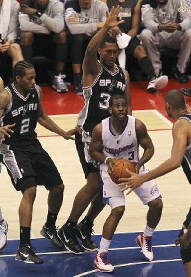 Surrounded by San Antonio Spurs Kawhi Leonard (02), Boris Diaw (33) and Tim Duncan (21), Los Angeles Clippers Chris Paul (03), looks for a way out of the paint during the second half of game three of the Western Conference semifinals at Staples Center in Los Angeles, Saturday, May 19, 2012.  Spurs defeated the Clippers, 96-86. Jerry Lara/San Antonio Express-News (San Antonio Express-News)