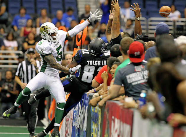 Fans try to catch the ball as receiver Burl Toler flies over the sideline barrier ahead of defender Andr Jones in the second quarter as the San antonio Talons play the San Jose Sabercats  on May 19, 2012.  Tom Reel/ San Antonio Express-News Photo: TOM REEL, San Antonio Express-News / San Antonio Express-News