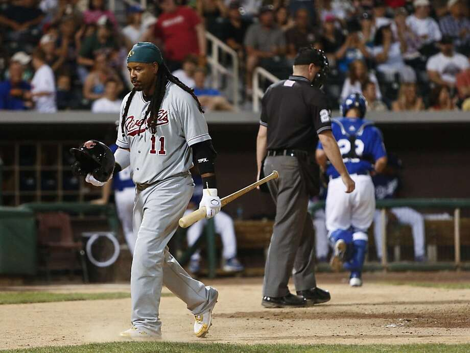 Manny Ramirez, playing for the Sacramento RiverCats, walks back to the dugout after striking out to end the top of the fifth inning in a Triple-A baseball game against the Albuquerque Isotopes in Albuquerque, N.M., Saturday, May 19, 2012. In advance of being activated from his 50-game suspension, Ramirez is scheduled to play 10 games with Sacramento before returning to the Oakland Athletics. (AP Photo/Jake Schoellkopf) Photo: Jake Schoellkopf, Associated Press