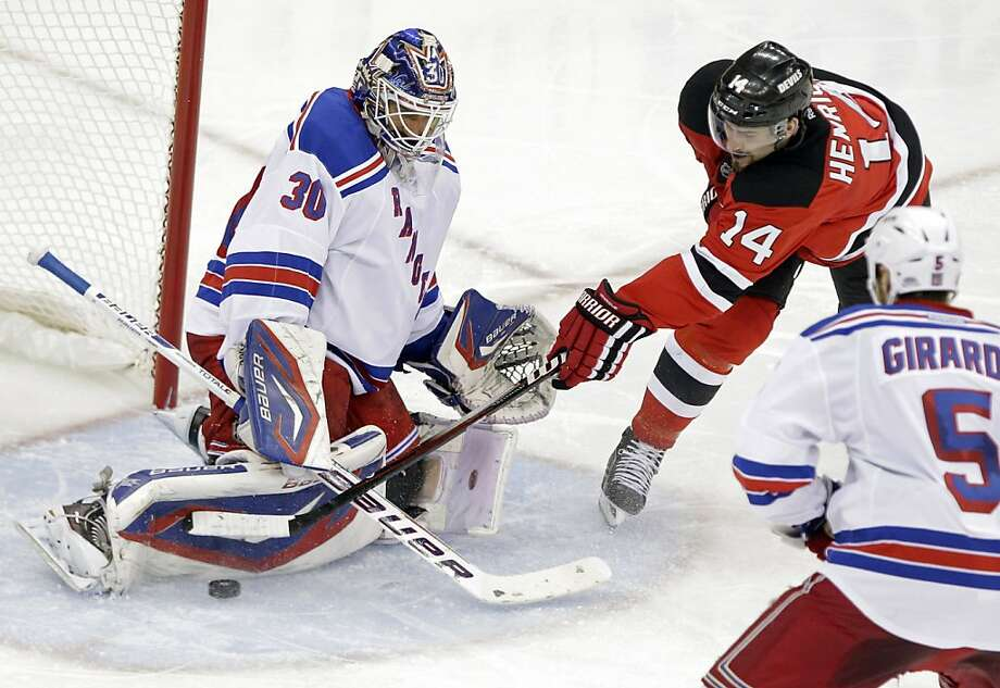 New York Rangers goalie Henrik Lundqvist, left, of Sweden stops a shot by New Jersey Devils center Adam Henrique as Rangers defenseman Dan Girardi skates in during the second period of Game 3 of an NHL hockey Stanley Cup Eastern Conference final playoff series, Saturday, May 19, 2012, in Newark, N.J.  (AP Photo/Frank Franklin II) Photo: Frank Franklin II, Associated Press