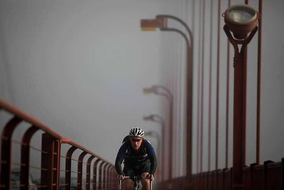Chased by a blanket of fog, an early morning bike commuter crosses the Golden Gate Bridge near the north tower on May 8, 2012 in San Francisco, Calif. Photo: Mike Kepka, The Chronicle
