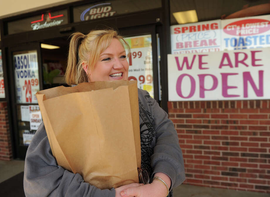 Kristie Entwistle of Stratford walks out of Super Saver Spirits on Bridgeport Avenue in Shelton on Sunday, May 20, 2012, the first day of Sunday liquor sales in the state of Connecticut. Entwistle said she made her Sunday wine purchase for a spontaneous get together with her sister. Photo: Brian A. Pounds / Connecticut Post