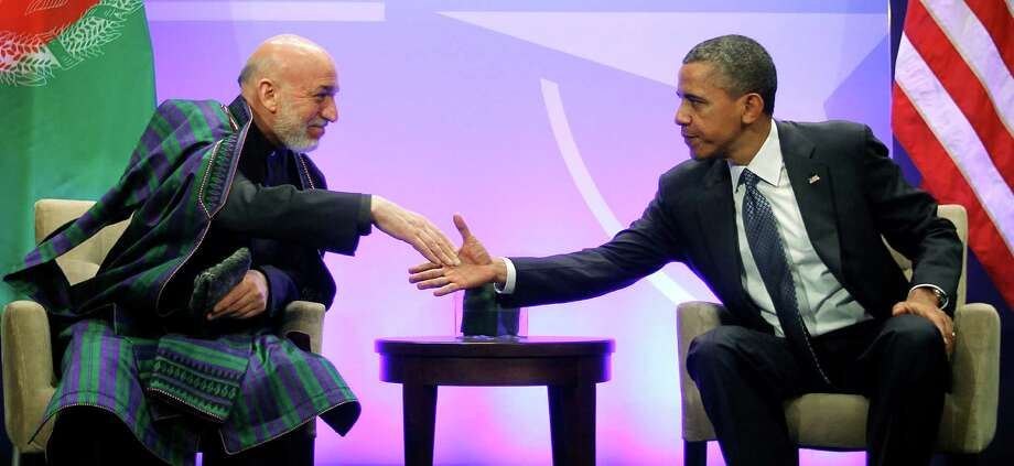 President Barack Obama (right) shakes hands with with Afghan President Hamid Karzai (left) during their meeting at the NATO Summit in Chicago, Sunday, May 20, 2012. Karzai thanked Americans for the help their 'taxpayer money' has done in Afghanistan. Photo: Pablo Martinez Monsivais, Associated Press