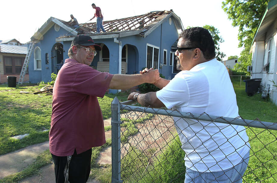 Paul Lankford (left) talks with friend David Saldivar in front of their homes. Neighbors and friends are among those helping to fix Lankford's leaky roof. Photo: Kin Man Hui, San Antonio Express-News / SAN ANTONIO EXPRESS-NEWS