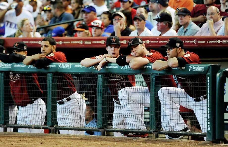 Houston Astros players watch the first inning of an interleague baseball game against the Texas Rangers, Sunday, May 20, 2012, in Houston. The Rangers scored five runs in the first on their way to a 6-1 win. (AP Photo/Pat Sullivan) Photo: Pat Sullivan, Associated Press / AP