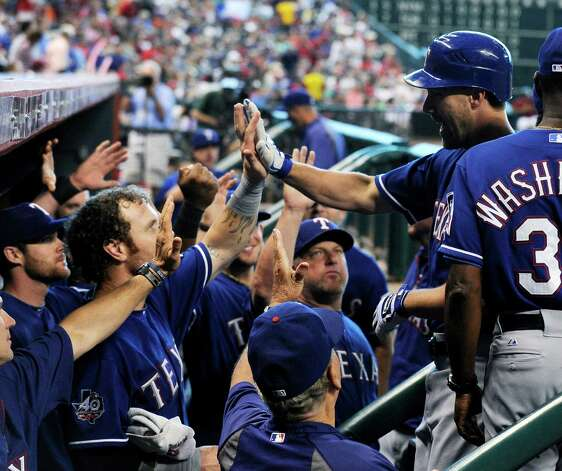 Texas Rangers' David Murphy, right, is welcomed back to the dugout after hitting a solo home run against the Houston Astros in the fifth inning of an interleague baseball game, Sunday, May 20, 2012, in Houston. Photo: AP