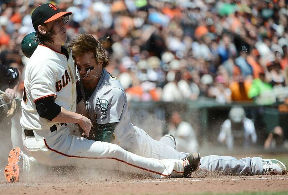 SAN FRANCISCO, CA - MAY 20:  Collin Cowgill #12 of the Oakland Athletics scoring from second base on a wild pitch, collides at home-plate with pitcher Tim Lincecum #55 of the San Francisco Giants in the fourth inning at AT&T Park on May 20, 2012 in San Francisco, California.  (Photo by Thearon W. Henderson/Getty Images) Photo: Thearon W. Henderson, Getty Images