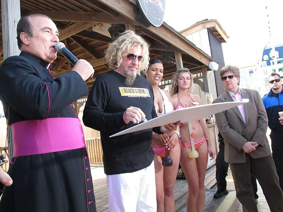 Monsignor William Hodge of St. Nicholas Roman Catholic Church in Atlantic City N.J., left, thanks rocker Sammy Hagar for a $10,000 donation to his church's food pantry on May 18, 2012. The former Van Halen singer told The Associated Press he's not surprised the Van Halen tour appears to be crumbling, with dozens of dates postponed. (AP Photo/Wayne Parry) Photo: Wayne Parry, Associated Press