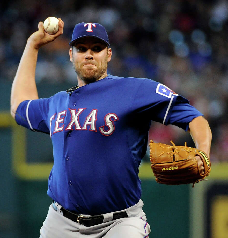 Texas Rangers' Colby Lewis delivers a pitch against the Houston Astros in the first inning of an interleague baseball game, Sunday, May 20, 2012, in Houston. Photo: AP
