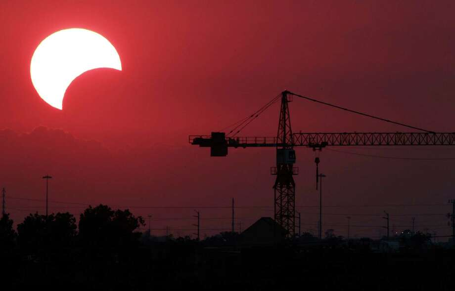 "The moon begins to partially block the sun as the sun sets at 8:02 p.m. silhouetting a crane just west of downtown Houston during a rare solar eclipse known as the ""ring of fire"" Sunday, May 20, 2012, in Houston. Photo: Johnny Hanson, Houston Chronicle / © 2012  Houston Chronicle"