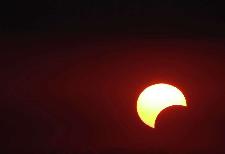 "The moon begins to partially block the sun as the sun sets at 8:02 p.m. in a photograph taken from a parking garage in downtown Houston during a rare solar eclipse known as the ""ring of fire"" Sunday, May 20, 2012, in Houston. Photo: Johnny Hanson, Houston Chronicle / © 2012  Houston Chronicle"