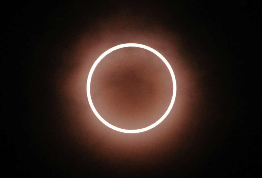 An annular solar eclipse is seen from Tokyo on May 21, 2012 . For the first time in 932 years, a swathe of the country was able to see the annular solar eclipse, when the moon passes in front of the sun, blocking out all but an outer circle of light.   AFP PHOTO / KAZUHIRO NOGIKAZUHIRO NOGI/AFP/GettyImages Photo: KAZUHIRO NOGI, AFP/Getty Images / AFP