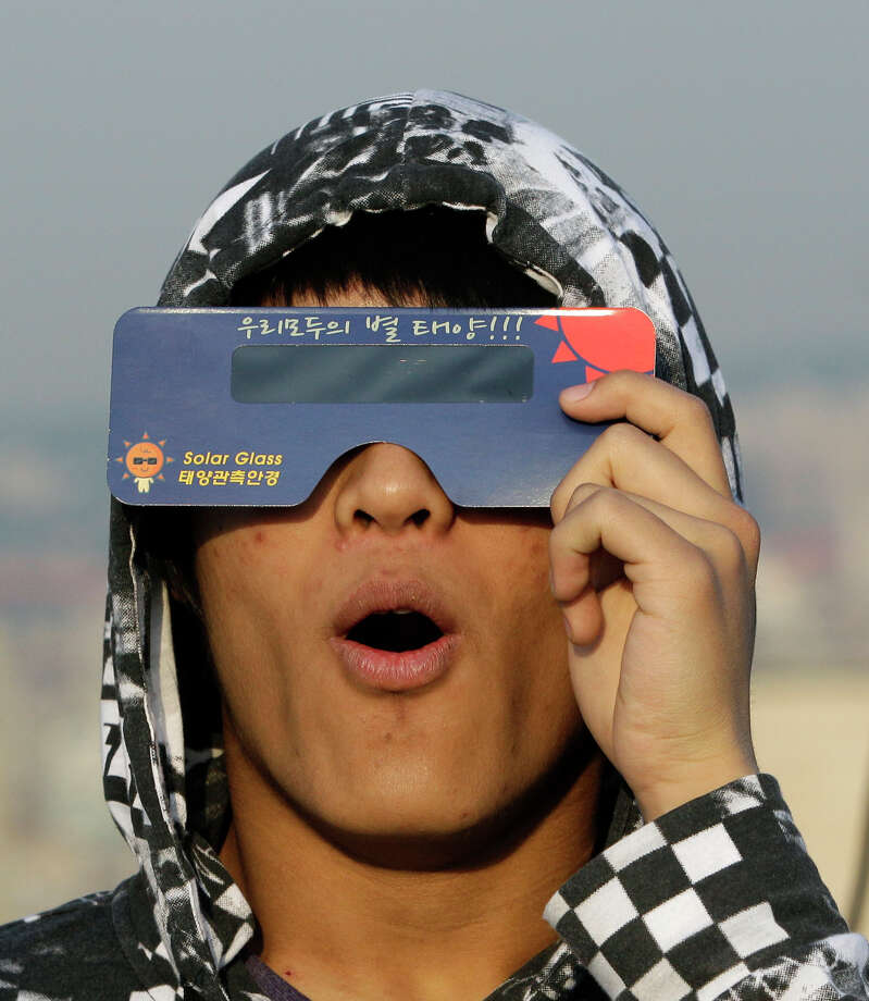 "A South Korean astronomy student uses special sunglasses to observe an annular solar eclipse in Seoul, South Korea, Monday, May 21, 2012. Millions of Asians watched as a rare ""ring of fire"" eclipse crossed their skies early Monday. The annular eclipse, in which the moon passes in front of the sun leaving only a golden ring around its edges, was visible to wide areas across the continent. (AP Photo/Lee Jin-man) Photo: Lee Jin-man, Associated Press / AP"