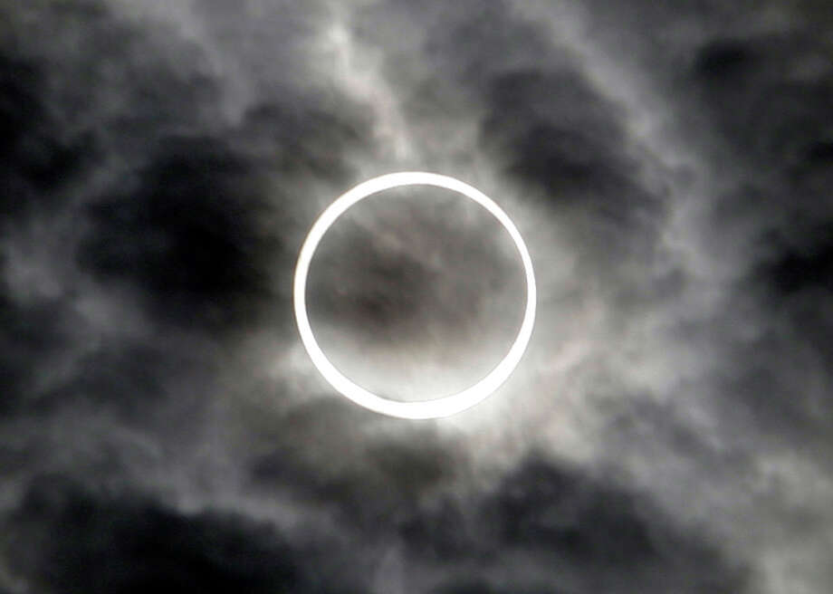 "An annular solar eclipse is seen in the sky over Tokyo Monday, May 21, 2012. Millions of Asians watched as a rare ""ring of fire"" eclipse crossed their skies early Monday. The annular eclipse, in which the moon passes in front of the sun leaving only a golden ring around its edges, was visible to wide areas across the continent. (AP Photo/Toru Takahashi) Photo: Toru Takahashi, Associated Press / AP"