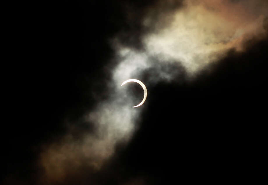 An annular solar eclipse is seen briefly during a break in clouds over Taipei, Taiwan, Monday, May 21, 2012. The annular solar eclipse, in which the moon passes in front of the sun leaving only a golden ring around its edges, was visible to wide areas across the continent Monday morning.  (AP Photo/Wally Santana) Photo: Wally Santana, Associated Press / AP