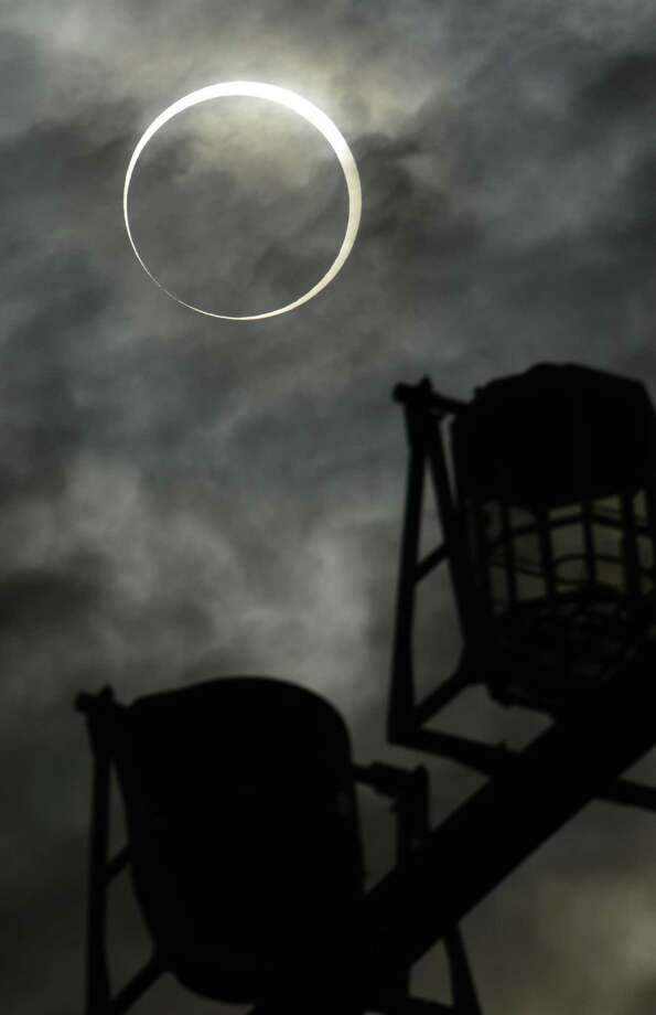 An annular solar eclipse is seen behind a ferris wheel from Tokyo on May 21, 2012.  For the first time in 932 years, a swathe of the country was able to see the annular solar eclipse, when the moon passes in front of the sun, blocking out all but an outer circle of light. Photo: YOSHIKAZU TSUNO, AFP/Getty Images / AFP