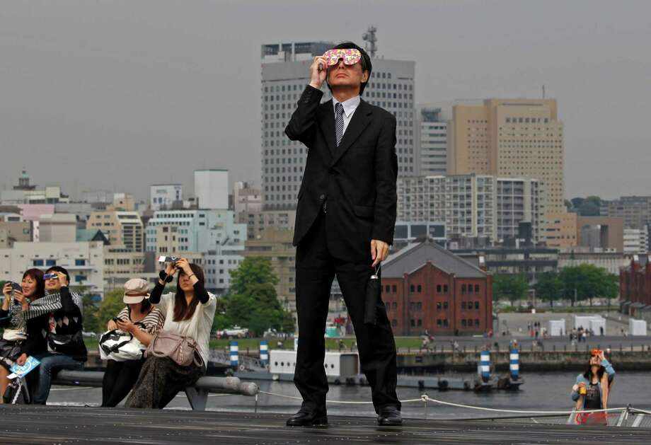"A business man watches an annular solar eclipse at a waterfront park in Yokohama, near Tokyo, Monday, May 21, 2012.  Millions of Asians watched as a rare ""ring of fire"" eclipse crossed their skies early Monday.  The annular eclipse, in which the moon passes in front of the sun leaving only a golden ring around its edges, was visible to wide areas across the continent. (AP Photo/Shuji Kajiyama) Photo: Shuji Kajiyama, Associated Press / AP"