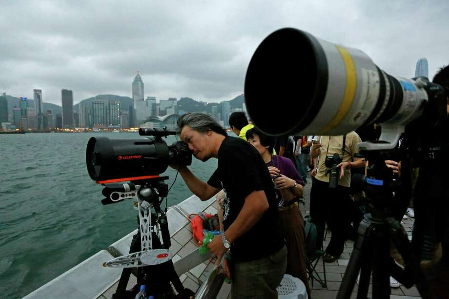"""Hong Kong stargazers use telescopes to observe an annular solar eclipse along the Victoria Habour in Hong Kong, Monday, May 21, 2012.  Millions of Asians watched as a rare """"ring of fire"""" eclipse crossed their skies early Monday. The annular solar eclipse, in which the moon passes in front of the sun leaving only a golden ring around its edges, was visible to wide areas across the continent Monday morning. (AP Photo/Vincent Yu) Photo: Vincent Yu, Associated Press / AP"""