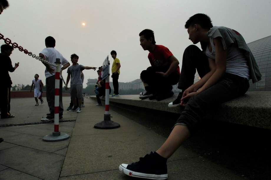 "Chinese youths, exercising outside the National Center for the Performing Arts, watch their friend run as a partial annular solar eclipse is seen over Beijing, China, Monday, May 21, 2012. Millions of Asians watched as a rare ""ring of fire"" eclipse crossed their skies early Monday. The annular eclipse, in which the moon passes in front of the sun leaving only a golden ring around its edges, was visible to wide areas across the continent. (AP Photo/Ng Han Guan) Photo: Ng Han Guan, Associated Press / AP"