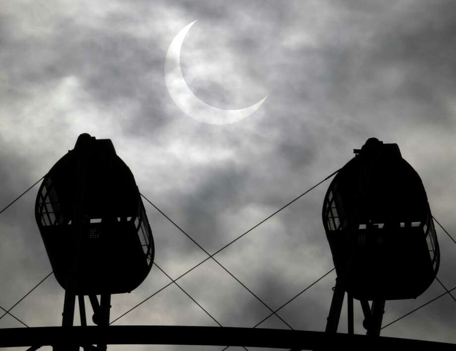 An annular solar eclipse is seen between Ferris wheel in the sky over Yokohama near Tokyo Monday, May 21, 2012.  The annular solar eclipse, in which the moon passes in front of the sun leaving only a golden ring around its edges, was visible to wide areas across the continent Monday morning. (AP Photo/Koji Sasahara) Photo: Koji Sasahara, Associated Press / AP