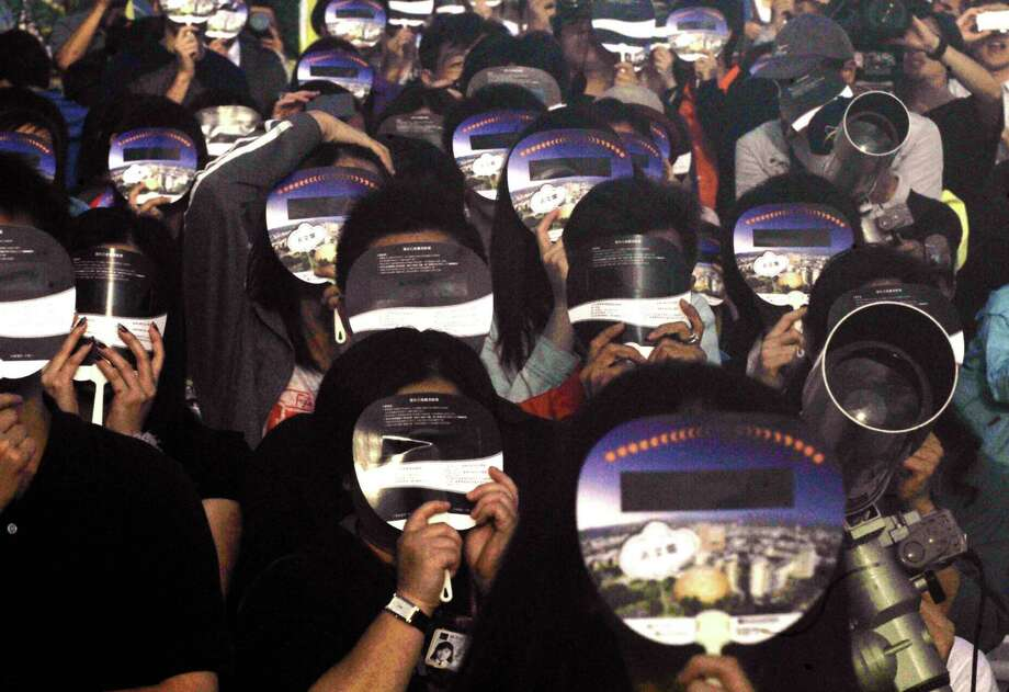 Astronomers watch the annular eclipse through eclipse-viewers in Taipei on May 21, 2012. The path of the eclipse will span 150-185 mile track that traverses eastern Asia, the northern Pacific Ocean and the western US, according to the US space agency. Photo: MANDY CHENG, AFP/Getty Images / AFP