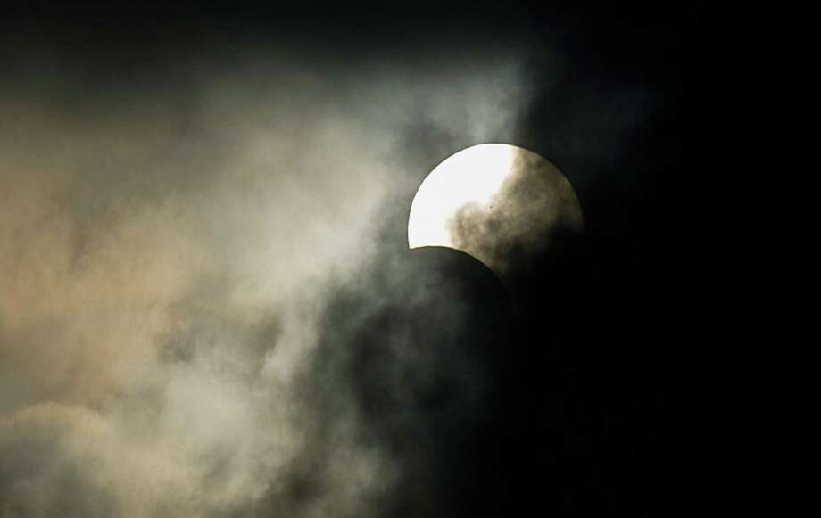 "A annular solar eclipse is seen between clouds in Hong Kong on May 21, 2012.  The path of the annular eclipse was to span ""a 150-185 mile track that traverses eastern Asia, the northern Pacific Ocean and the western US. Photo: PHILIPPE LOPEZ, AFP/Getty Images / AFP"