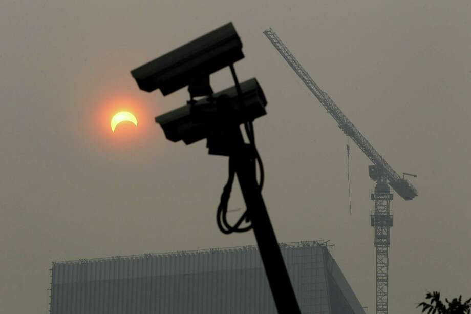 "Security cameras are silhouetted near a partial annular eclipse in Beijing, China, Monday, May 21, 2012. Millions of Asians watched as a rare ""ring of fire"" eclipse crossed their skies early Monday. The annular eclipse, in which the moon passes in front of the sun leaving only a golden ring around its edges, was visible to wide areas across the continent. (AP Photo/Ng Han Guan) Photo: Ng Han Guan, Associated Press / AP"