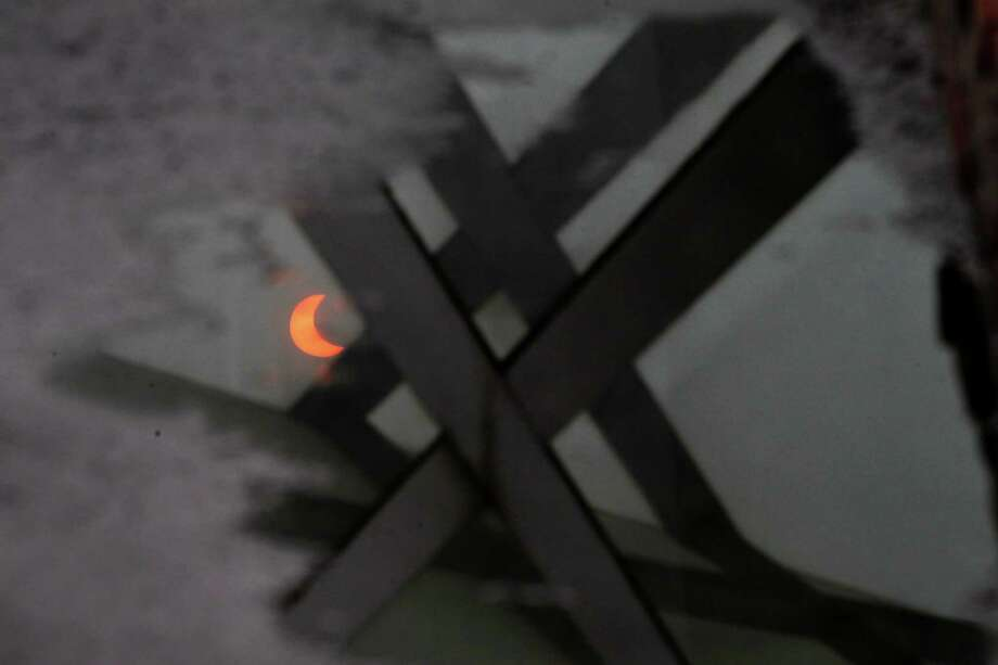 "A partial annular solar eclipse is reflected in a pool of water in Beijing, China, Monday, May 21, 2012. Millions of Asians watched as a rare ""ring of fire"" eclipse crossed their skies early Monday. The annular eclipse, in which the moon passes in front of the sun leaving only a golden ring around its edges, was visible to wide areas across the continent. (AP Photo/Ng Han Guan) Photo: Ng Han Guan, Associated Press / AP"