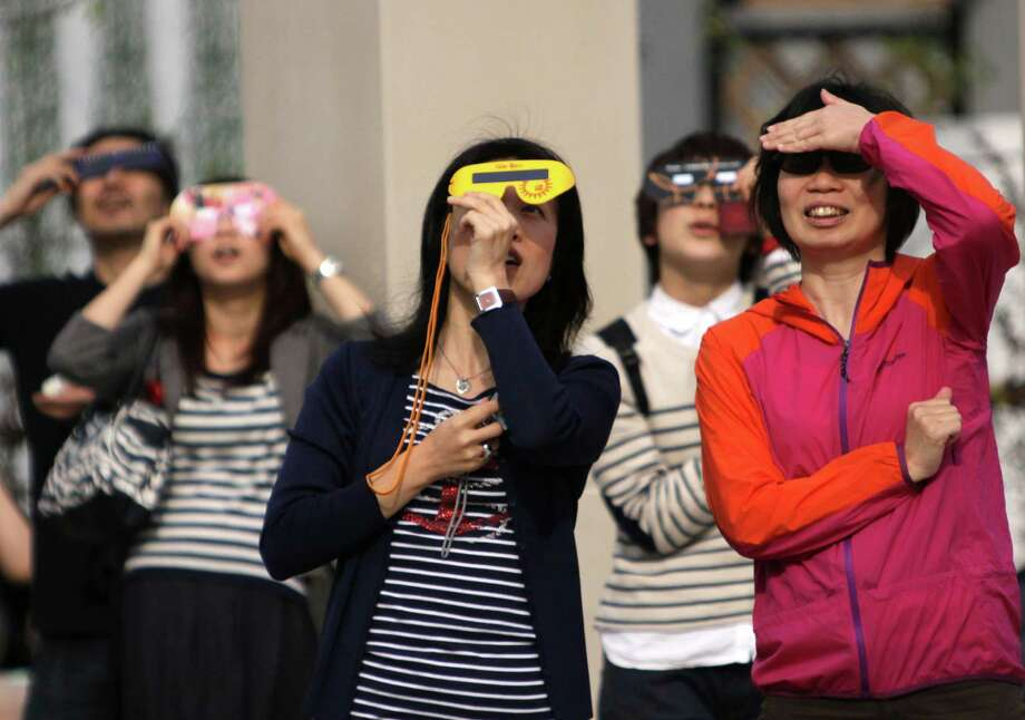 People observe a solar eclipse with special glasses in Tokyo on May 21, 2012 . For the first time in 932 years, a swathe of the country was able to see the annular solar eclipse, when the moon passes in front of the sun, blocking out all but an outer circle of light. Photo: YOSHIKAZU TSUNO, AFP/Getty Images / AFP
