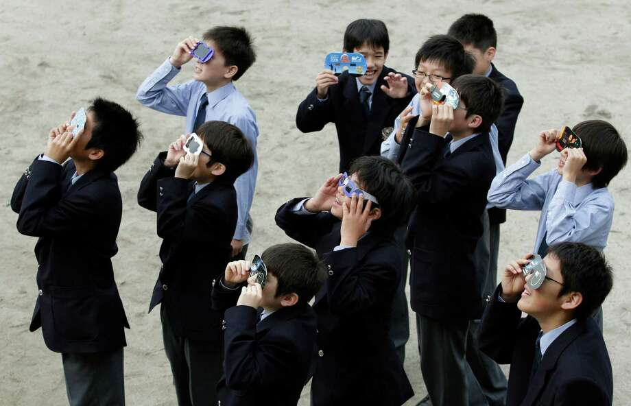 """High school students watch the annular solar eclipse in Fujisawa, near Tokyo, Monday, May 21, 2012. Millions of early risers in Asia turned their attention skyward to view a rare """"ring of fire"""" eclipse as it crossed their skies Monday morning. The annular eclipse, in which the moon passes in front of the sun leaving only a golden ring around its edges, was visible to wide areas across China, Japan and elsewhere in the region before moving across the Pacific to be seen in parts of the western United States. Photo: AP"""