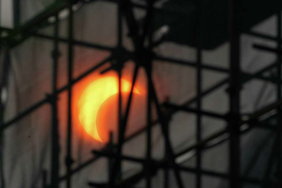 A partial annular solar eclipse appears through construction scaffoldings in Beijing, China, Monday, May 21, 2012. The annular eclipse, in which the moon passes in front of the sun leaving only a golden ring around its edges, was visible to wide areas across China, Japan and elsewhere in the region before moving across the Pacific to be seen in parts of the western United States. Photo: AP