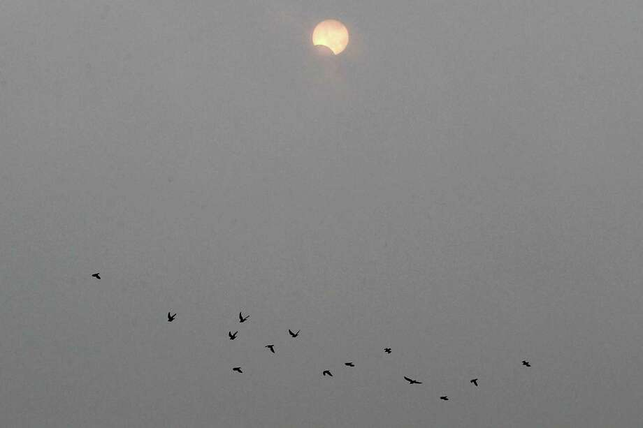 A flock of birds fly past a partial annular solar eclipse over Beijing, China, Monday, May 21, 2012. The annular eclipse, in which the moon passes in front of the sun leaving only a golden ring around its edges, was visible to wide areas across China, Japan and elsewhere in the region before moving across the Pacific to be seen in parts of the western United States. Photo: AP
