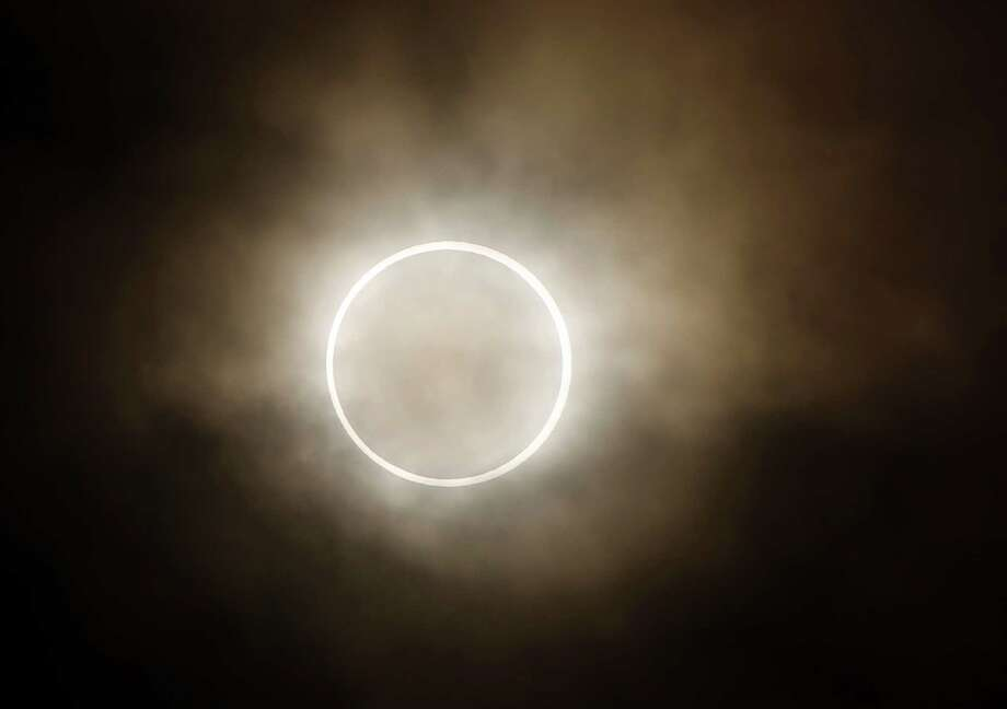 An annular eclipse appears at a waterfront park in Yokohama, near Tokyo, Monday, May 21, 2012. The annular eclipse, in which the moon passes in front of the sun leaving only a golden ring around its edges, was visible to wide areas across China, Japan and elsewhere in the region before moving across the Pacific to be seen in parts of the western United States. Photo: AP