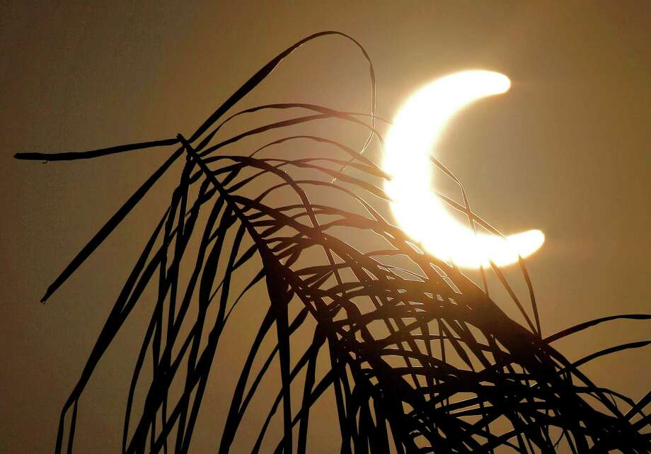 An annular solar eclipse appears Sunday, May 20, 2012, in Chandler, Ariz. The annular eclipse, in which the moon passes in front of the sun leaving only a golden ring around its edges, was visible to wide areas across China, Japan and elsewhere in the region before moving across the Pacific to be seen in parts of the western United States. Photo: AP