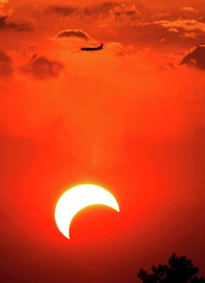 A passenger jet flies above an annular solar eclipse Sunday, May 20, 2012, in Irving, Texas. The annular eclipse, in which the moon passes in front of the sun leaving only a golden ring around its edges, was visible to wide areas across China, Japan and elsewhere in the region before moving across the Pacific to be seen in parts of the western United States. Photo: AP