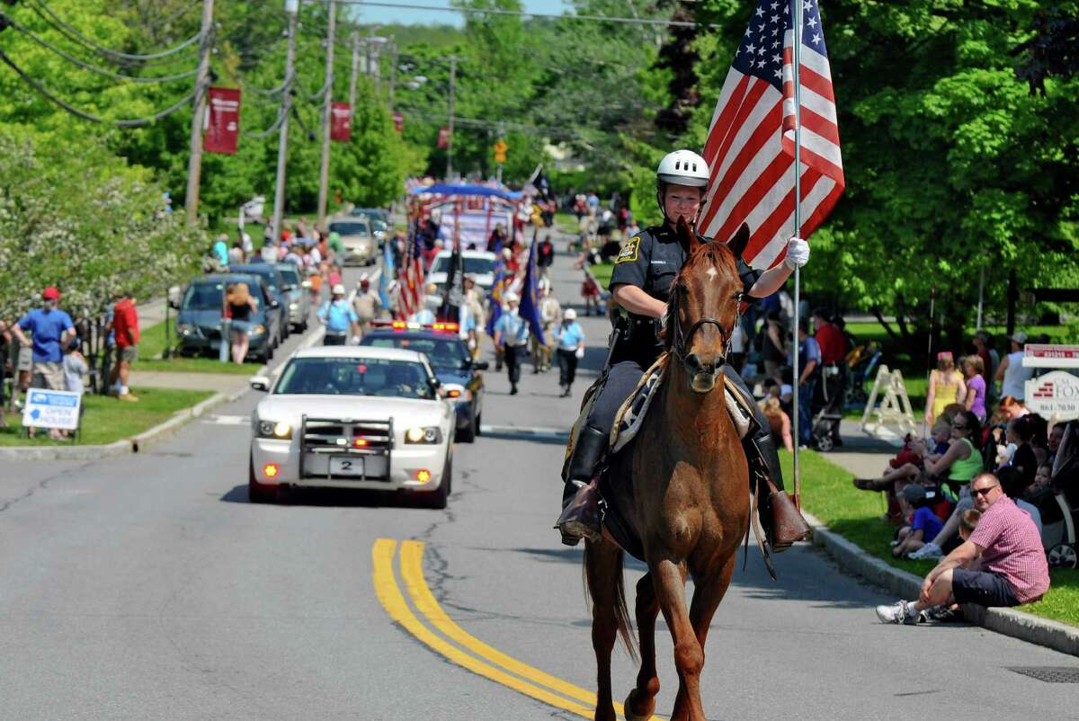 Altamont police officer Melanie Parkes rides Humphrey as she carries the American flag at the head of the annual Memorial Day parade on Main Street, on Sunday May 20, 2012 in Altamont, NY. (Philip Kamrass / Times Union )