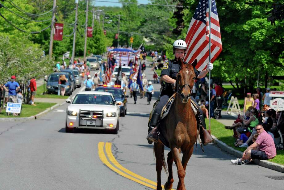 Altamont police officer Melanie Parkes rides Humphrey as she carries the American flag at the head of the annual Memorial Day parade on Main Street, on Sunday May 20, 2012 in Altamont, NY. (Philip Kamrass / Times Union ) Photo: Philip Kamrass / 00017641A