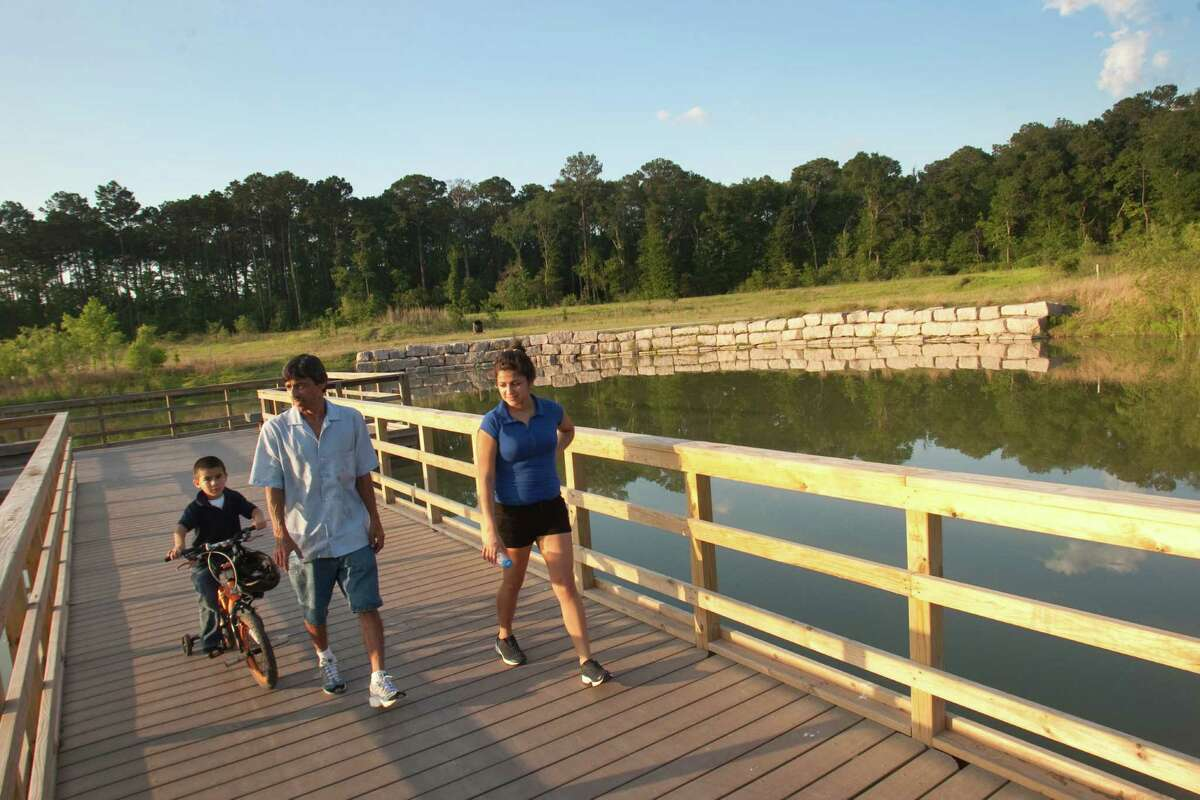 Jose Espinoza goes for a stroll with his daughter, Aracely, and his grandson Manuel, 5, at a floodwater detention pond that doubles as Keith-Weiss park.
